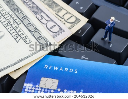 miniature businessman standing on the computer keyboard with credit card and US dollar banknote - stock photo