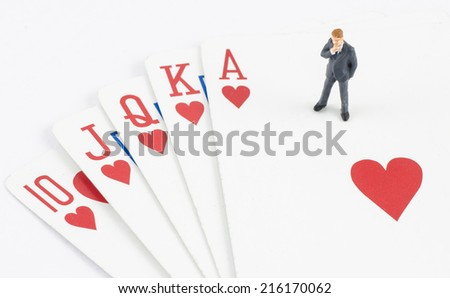 miniature businessman standing on the gamble card - stock photo