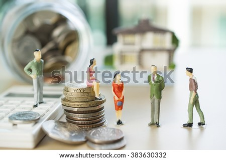 Miniature businessman team with blur gold stack of coins   - stock photo