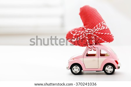 Miniature car carrying a red heart cushion  - stock photo