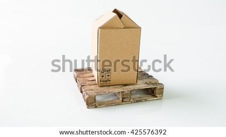 Miniature cardboard box with Fragile wording symbol on wooden pallet. Concept of handle with care or courier business. Isolated on white background. Slightly de-focused and close-up shot. Copy space. - stock photo
