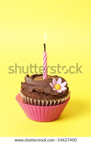 Miniature chocolate cupcake with icing, decorative flower and birthday candle on yellow background - stock photo