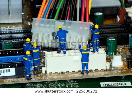 Miniature construction worker figurines posed as if working on a computer motherboard. - stock photo