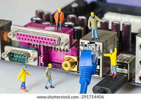 Miniature engineer team try to connect ethernet cables to port - stock photo