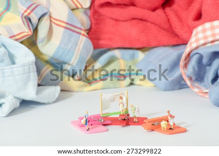 Miniature figure of woman doing laundry concept  - stock photo