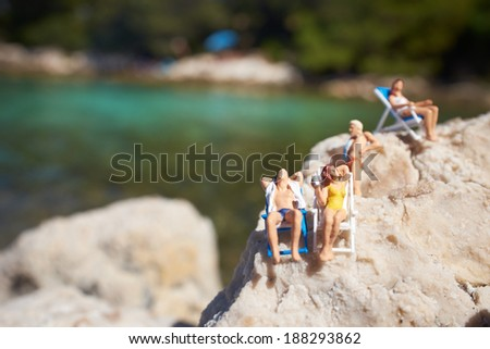 Miniature figurine an a beach in swimming costume - stock photo