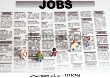 miniature figurine of people standing in front of jobs  seeking offerings - stock photo