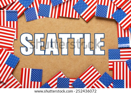 Miniature flags of the United States of America form a border on brown card around the name of the city of Seattle