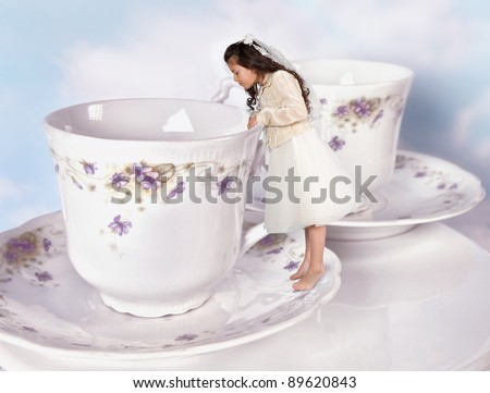 Miniature girl in alice in wonderland dress shrunk to the size of a teacup - stock photo
