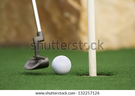 miniature golf ball near the hole and putter - stock photo