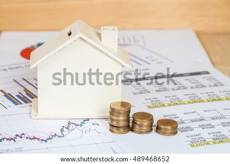 Miniature house with money and chart