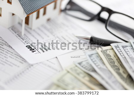 Miniature house with money and tax papers. - stock photo