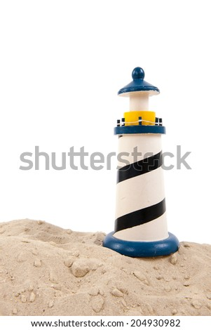 Miniature lighthouse at the beach on white background