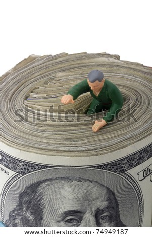 Miniature man getting out of a roll of American money. - stock photo