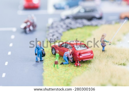 Miniature mechanics replacing a tyre off the roadway - stock photo