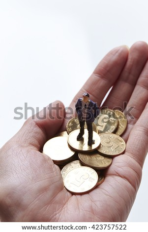 Miniature men and coins on hand