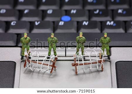 Miniature military soldiers and barbed wire are guarding a laptop from viruses, spyware and identity thieves. Computer security concept. - stock photo