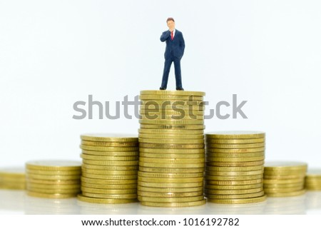 Miniature people : Businessman standing on stack of coins. Image use for business concept.
