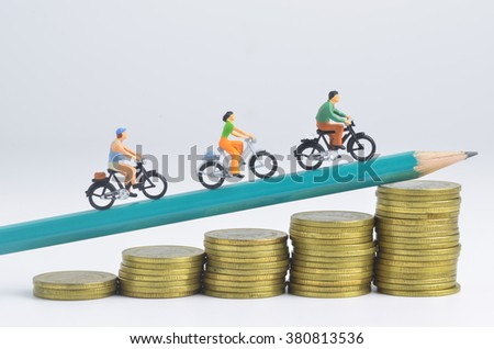 Miniature people cycling on pencil and stack of coins - stock photo