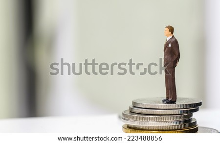 Miniature people on coins  - stock photo