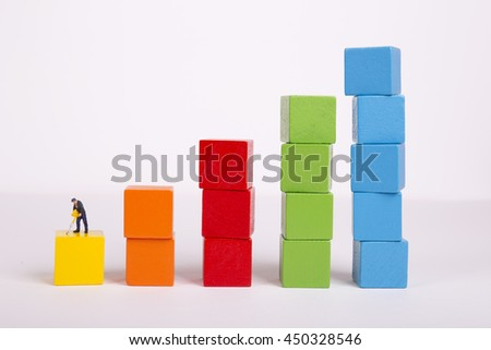 Miniature people on stack of colorful wooden cube building blocks, worker digging on colorful wooden cube. - stock photo