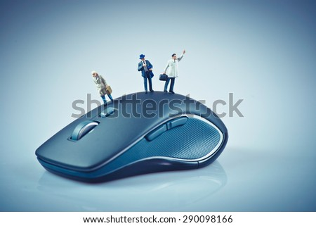 Miniature people on top of computer mouse. Business concept. Macro photo - stock photo