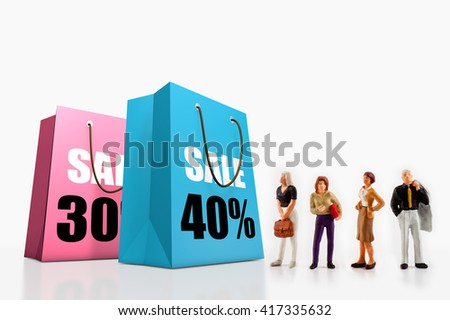miniature people  - people standing in front of paper bags with printed big sale.  - stock photo