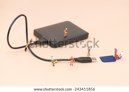 Miniature people team working to transfer and back up data concept - stock photo