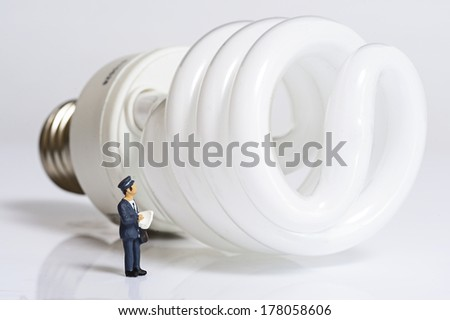 Miniature people with electric bulb - stock photo