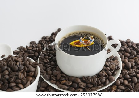 Miniature people with paddle boat in the coffee cup. - stock photo