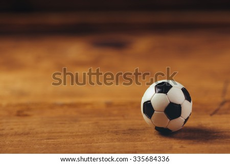 Miniature plastic soccer ball on wooden table with copy space, retro toned selective focus - stock photo