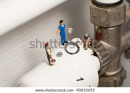 Miniature Plumbers Repairing A Thermostat. A team of miniature toy plumbers repiar a thermostat in a career and employment concept. - stock photo