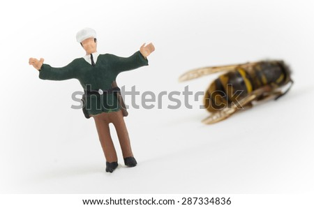 Miniature police officer guarding a crime scene - dead wasp - isolated - stock photo