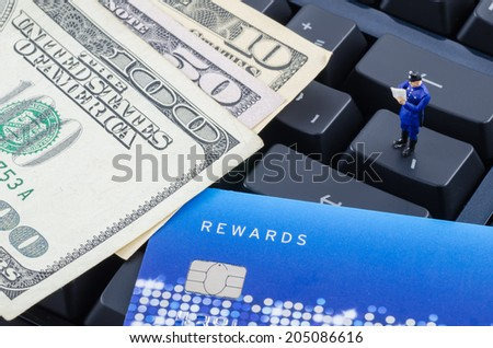 miniature policeman standing on the computer keyboard with US banknote, Internet security concept