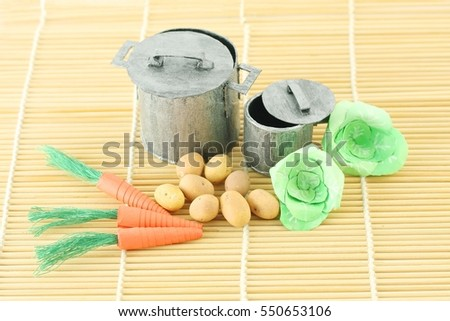 miniature pots and vegetables hand crafted, on bamboo sushi rolling mat