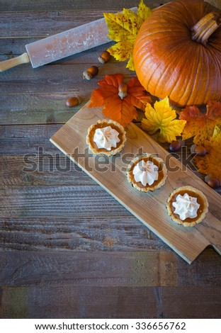 Miniature pumpkin pies displayed on a wood table