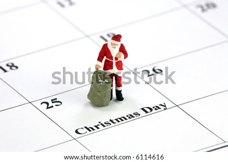 Miniature Santa Claus standing on a calendar with Christmas Day printed on it. Christmas concept. - stock photo