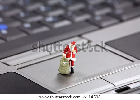 Miniature Santa Claus standing on a laptop.  Christmas shopping online concept. - stock photo