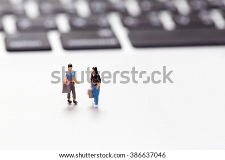 Miniature shopper with shopping bag on a laptop keyboard. Online shopping concept.
