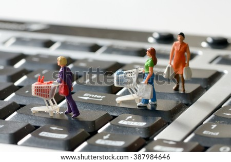 Miniature shoppers  with shopping cart on a computer keyboard - stock photo