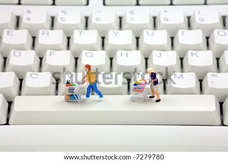 Miniature shoppers with shopping carts on a computer keyboard. Online shopping concept. - stock photo