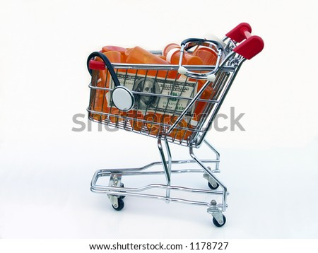 Miniature shopping cart isolated on white filled with prescription bottles, a US one hundred dollar bill and a stethoscope illustrating the high cost of prescriptions.