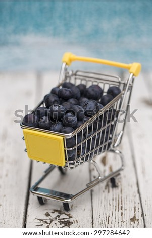 Miniature shopping cart with blueberries - stock photo