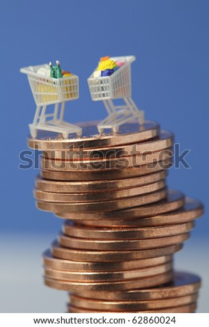 Miniature shopping carts on top of euro coin stack - stock photo