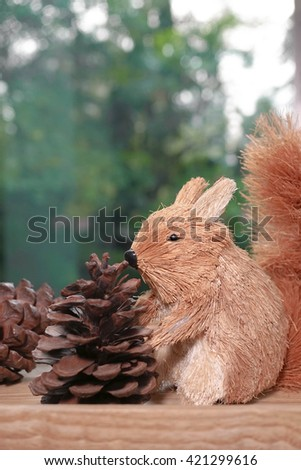Miniature squirrel and pine cones by the window, abstract blur tree background (animal gathering food for winter hibernation concept) - stock photo
