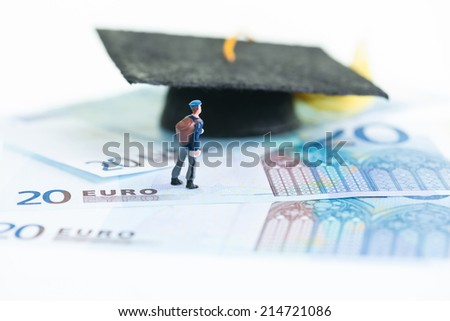Miniature student and the mortarboard close up - stock photo