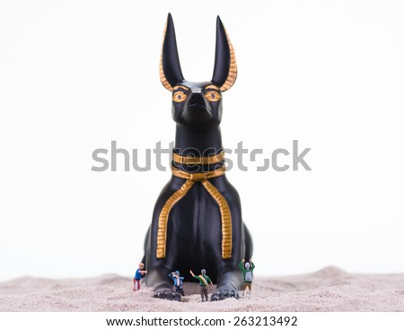 Miniature tourists with the Egyptian God Anubis statue on sand close up - stock photo