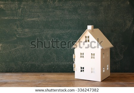 miniature toy house over chalkboard background. room for text - stock photo