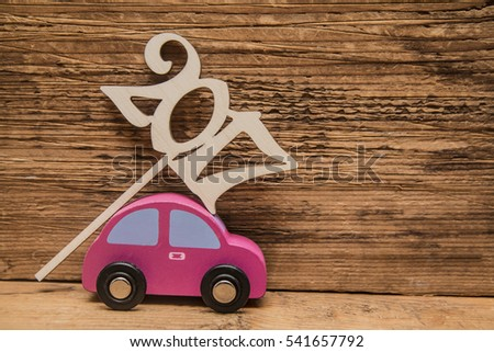 Miniature toy retro vintage car carrying wooden numbers - 2017 on wooden board background. Happy New Year idea, symbol.