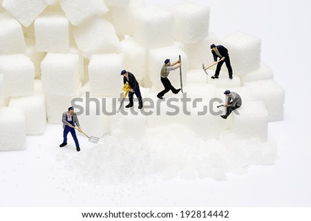 Miniature toy worker work with sugar - stock photo